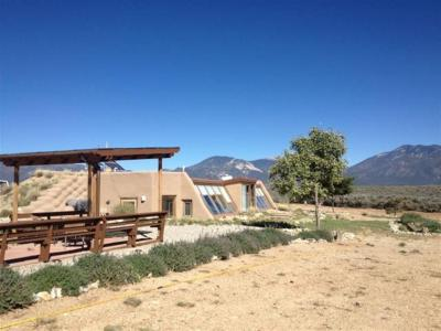 Fabulous off grid home.Self sufficient passive solar with water catchment. This 2 bedroom, 1 bath Earthship sits on 5 acres that border pueblo land and has endless views. Completely custom. Brick and wood floors, vigas, kiva fireplaces