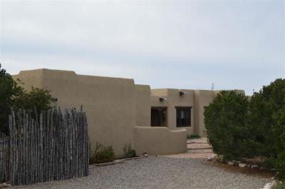 Overlooking the Valley, surrounded by Piñon and Juniper sits this stunning Adobe home. Patios off the Master Bedroom suite, dining room and front of home, with covered portal for lazy summer days. Home offers 3 Kiva Fireplaces, Chefs Kitchen with 6 burner Wolf stove, Dbl. Ovens and Granite counter-tops. Floor to ceiling windows with panoramic views and terrific light. Room with outside entrance, fabulous painting studio or Professional office. Oversized 2 car garage easily converted to whatever you like.